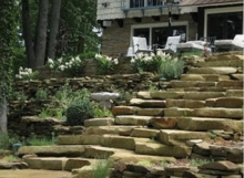 Blend natural stone steps with outcropping and wall stone to create a beautiful landscape.