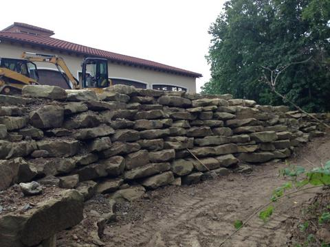 Natural stone retaining wall featuring Napoleon Stone's semi-stackable outcropping.
